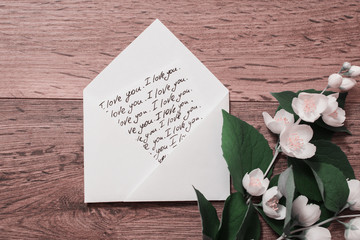 "The inscription ""I love you"" writing on the envelope calligraphy. Flowers and jasmine petals on wooden background. Greeting card. Conceptual photography. Wedding invitation card. Valentine day.;"
