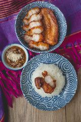 deep fried pork with sticky rice on thai fabric and old wooden,