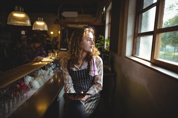 Thoughtful waitress looking through window in cafe