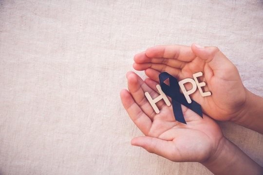 HOPE word with black ribbon on hands, for Skin cancer awareness, Melanoma Awareness,Narcolepsy Awareness and Mourning