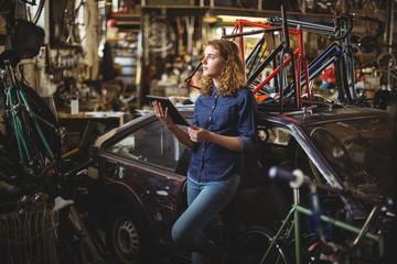 Mechanic using digital tablet while repairing bicycle