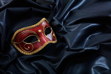 Carnival mask isolated on black satin background, copy space