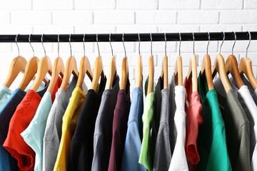 Colorful t-shirts on hangers against brick wall, close up view