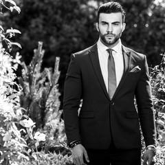 Black-white outdoor portrait of elegant handsome man in classical suit.