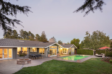 Luxury home with swimming pool at sunset with outdoor furniture.