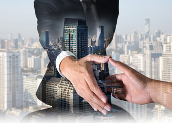 Double exposure of businessman will handshaking for business relationship and cityscape in the morning as Commitment and Partnership concept.