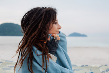 attracrive girl with dreadlocks covered with plaid on beach
