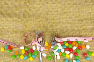 Diet and healthy teeth concept - Colorful candies fork and tape measure with shallow depth of field (dof)