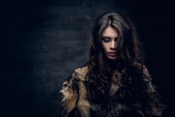Brunette female dressed in a fur jacket.