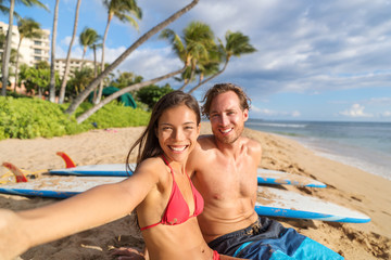 Happy young interracial couple taking phone selfie picture relaxing sitting near surfboards on beach holiday having fun doing surfing activity class. Travel vacation destination watersports.