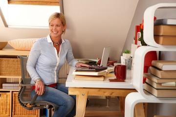 Happy woman sitting at desk