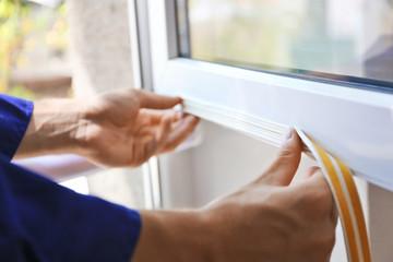 Fototapeta Construction worker putting sealing foam tape on window in house obraz