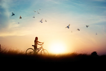 Lonely woman with bicycle on road of paddy field among flying birds