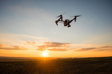 White drone with digital camera flying in sky over field on sunset