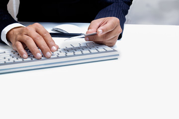 Man's hands holding a credit card and using pc for online shopping