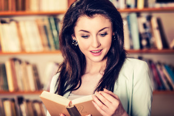 Young woman reading a book in front of bookshelves