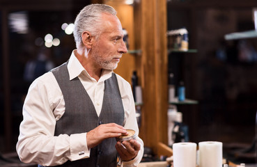 Senior businessman with hair gel in front of mirror