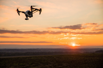 Foto op Textielframe Helicopter quadrocopter drone with remote control. Dark silhouette against colorfull sunset.