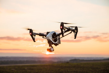 quadrocopter drone with remote control. Dark silhouette against colorfull sunset.