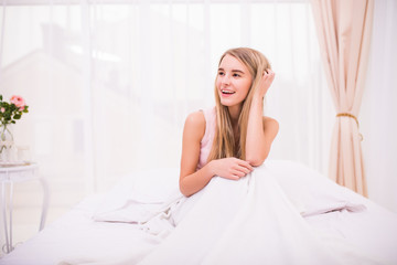 Young beautiful girl in morning bed with good mood