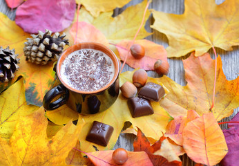 Autumn Cup of coffee, nuts, pine cones, chocolate and autumn leaves