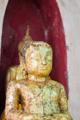 Closeup of the face and hands of buddha's image covering with go