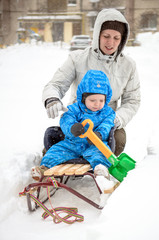 Young mother and little boy enjoying sleigh ride. Child sledding. Toddler kid riding sledge. Children play outdoors in snow. Kids sled in snowy park. Outdoor winter fun for family Christmas vacation