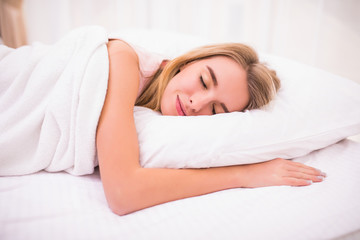 view of tired beautiful young woman with long hair sleeping on bed in bedroom
