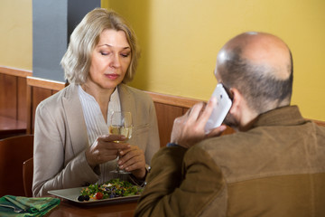 elderly woman bored in a restaurant while her man talking on the