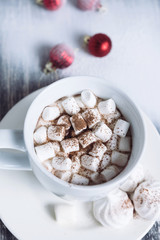 Hot chocolate with marshmallows. Drink in a white ceramic cup with zephyr on wooden snow table. Red balls