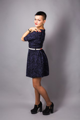 Fashionable beautiful young woman posing in studio. Girl with black short haircut.
