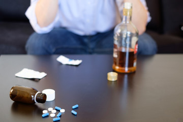 Depressed man mixing alcohol and pills