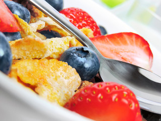 Breakfast bowl with cornflakes, blueberries and strawberries. Close-up shot with spoon and white bowl. Breakfast scene.
