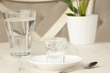 empty glasses and a spoon on a white table with a flower