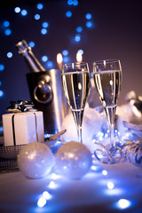 dim light white silver and blue romantic new year eve or christmas table in a luxury restaurant with champagne