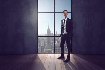 Geschäftsmann steht vor Fenster in Hochhaus