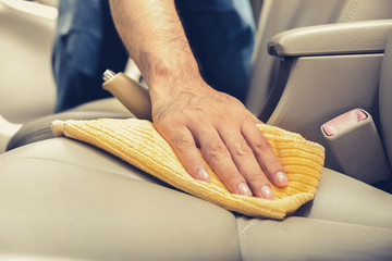 A man cleaning leather car seat with microfiber cloth