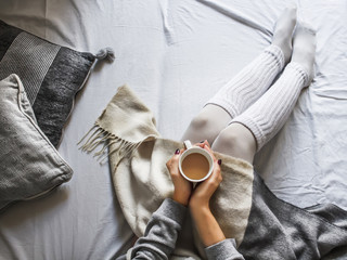 girl holding a cup of hot coffee on a cold winter morning at home in bed