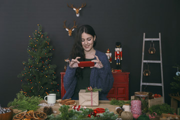 Smiling young woman photographing decorated Christmas gift with smartphone