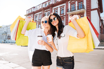 Women with shopping bags having fun walking on the street