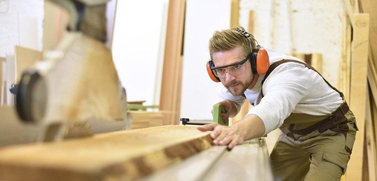 Carpenter using sawing machine in his workshop