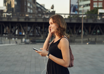 Germany, Young woman in Hamburg using smart phone