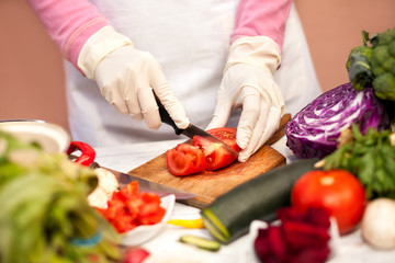 Woman with gloves slicing tomato with a knife in the kitchen