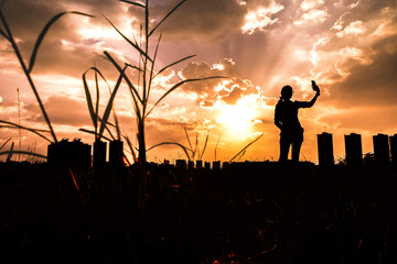 silhouette of young woman taking photo sunrise with smartphone Lifestyle concept, copy space
