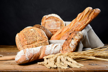 still life of assortment of traditional loaf of bread and baguette with wheat on wood table
