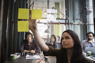 Business people looking at female colleague sticking adhesive note on window