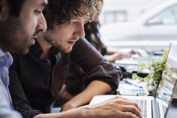 Two men working on laptop