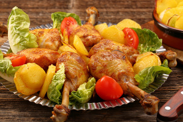 Chicken legs and baked potatoes with vegetable