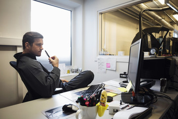 Confident male owner looking at computer monitor in office