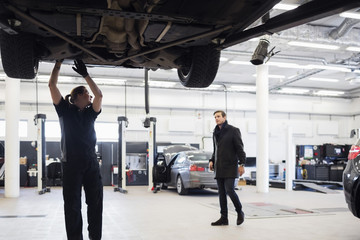 Mechanic looking at customer while working under car at repair shop